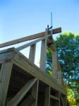 Ridge pole wedged with 2x4 cut offs and clamped