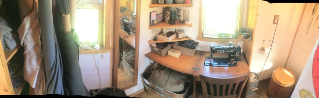 Pink room/bathroom panorama. Left to right: clothing storage, bolts of merino wool fabric, sewing machine and storage, bathroom and composting toilet
